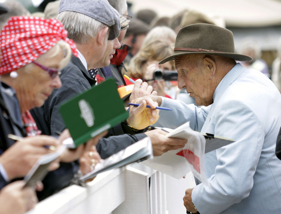 Sir Stirling Moss signs autographs for fans