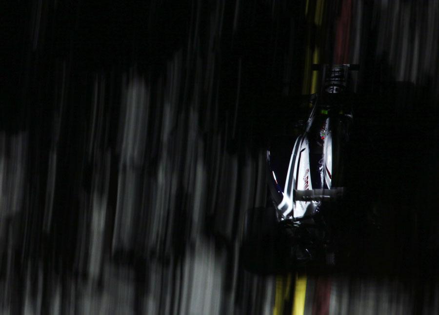 Rubens Barrichello flashes through the shadows