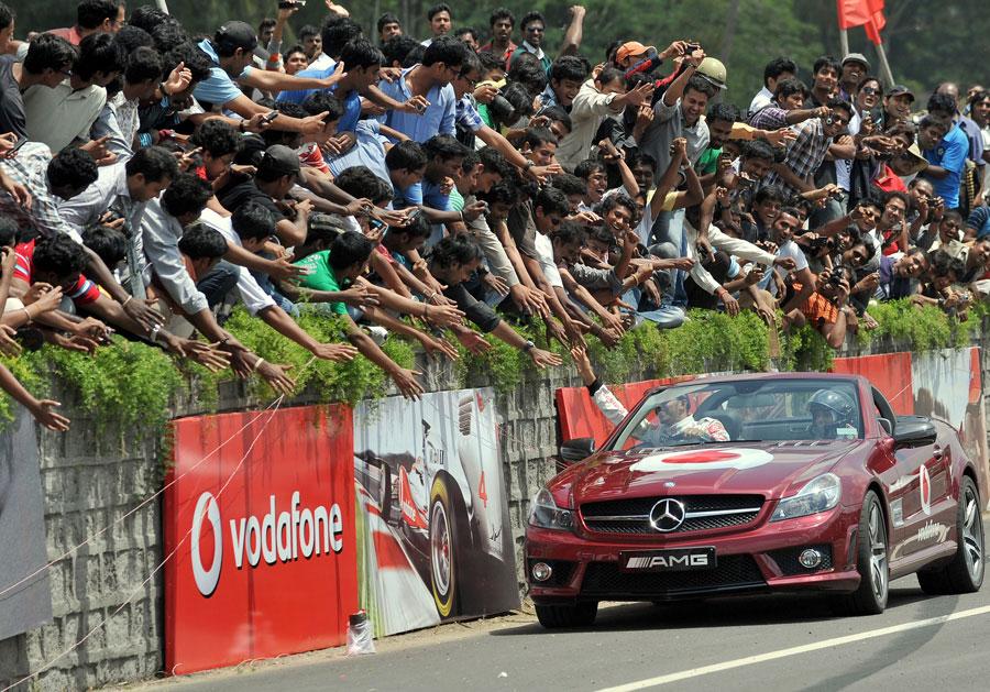 Lewis Hamilton acknowledges fans during a promotional event