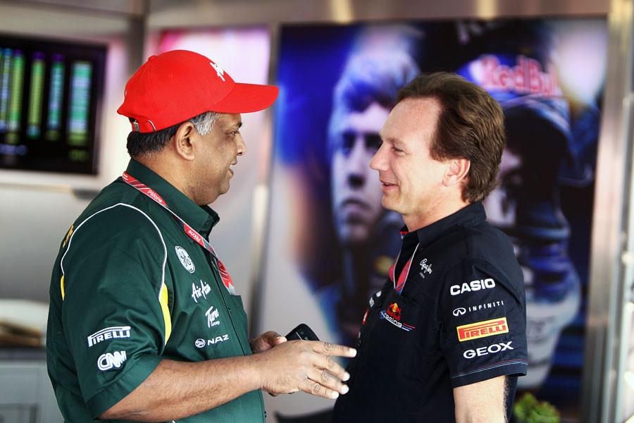 Tony Fernandes talks to Christian Horner in the Red Bull garage