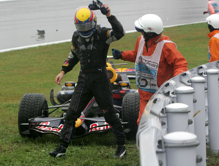 A furious Mark Webber heads for safety after a collision with Sebastian Vettel put him out of the race