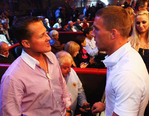 German footballer Lukas Podolski speaks to Michael Schumacher
