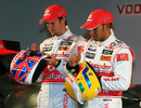 Jenson Button and Lewis Hamilton show off their helmet designs
