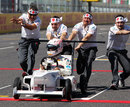 Kamui Kobayashi takes part in a soapbox race down the Suzuka pit straight