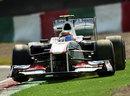 Sergio Perez slides his Sauber onto the artificial grass