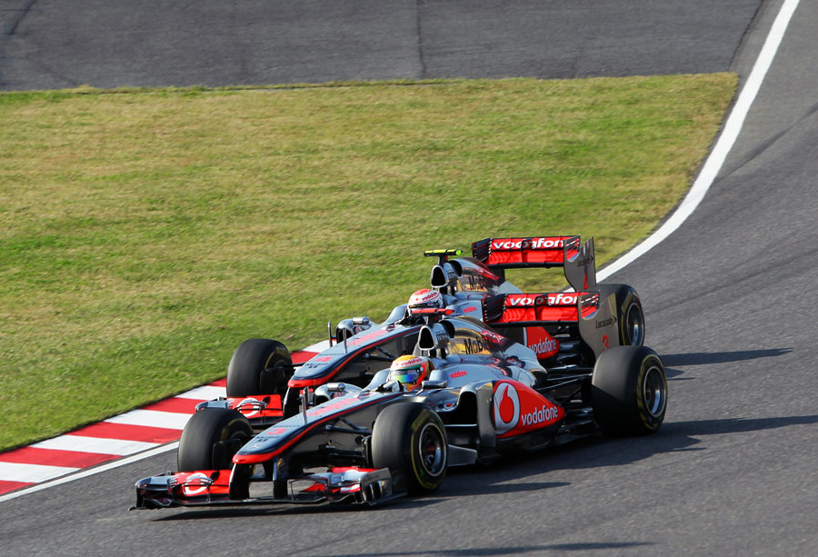 Lewis Hamilton gets around the outside of Jenson Button in to turn one