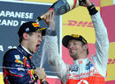 Race winner Jenson Button soaks championship winner Sebastian Vettel on the podium