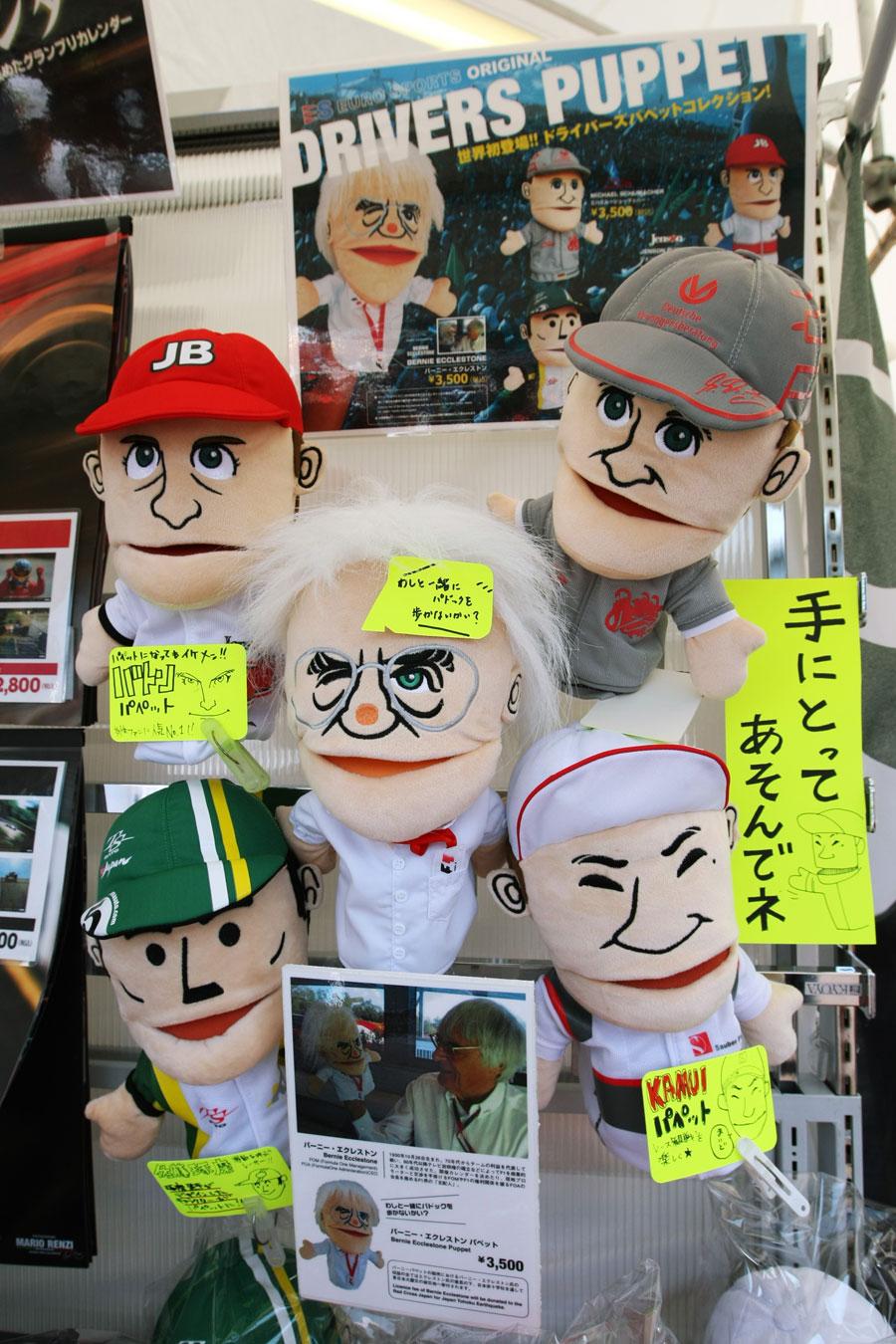 Bernie Ecclestone, Jenson Button, Michael Schumacher, Kamui Kobayashi and Takuma Sato hand puppets in the paddock