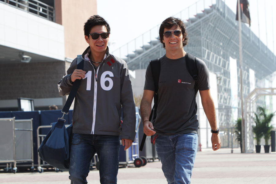 Kamui Kobayashi and Sergio Perez share a joke in the paddock
