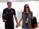 Jenson Button and Jessica Michibata walk through the paddock