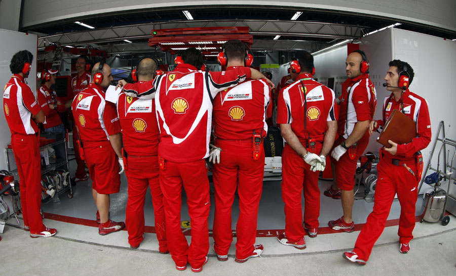 Ferrari crowd around the front of Fernando Alonso's car to conceal its new front wing