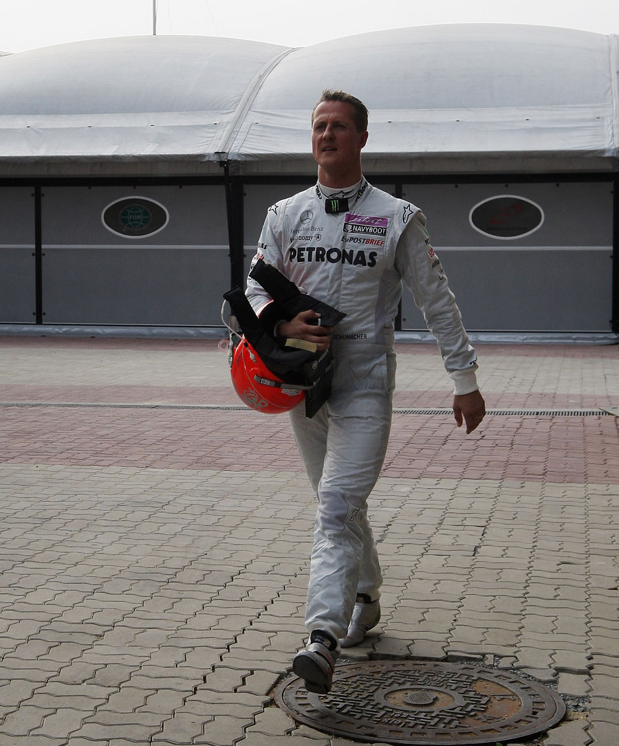 Michael Schumacher returns to the paddock after his race came to a premature end
