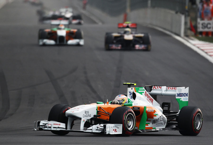 Paul di Resta tackles turn three as Sebastien Buemi lines up the other Force India of Adrian Sutil