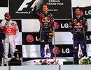 Sebastian Vettel celebrates on the podium alongside Lewis Hamilton and Mark Webber