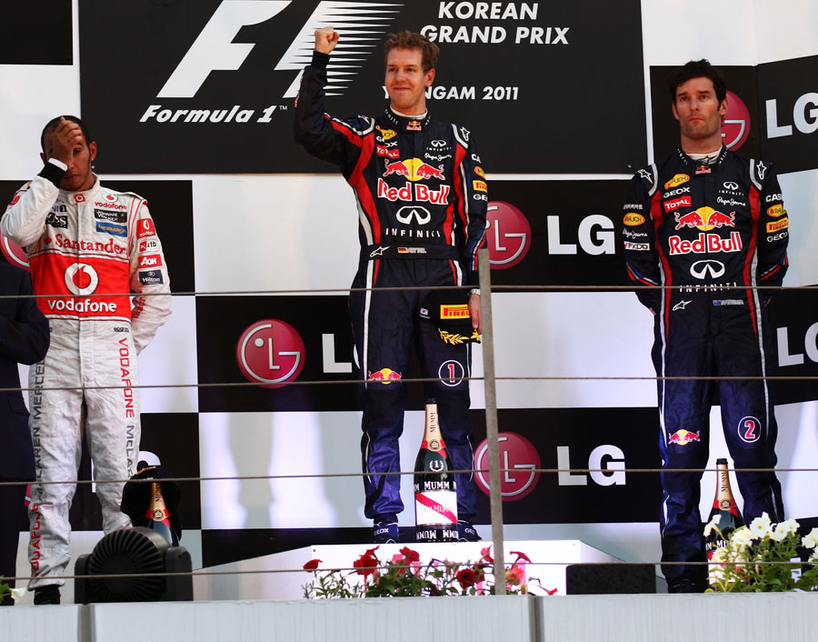 Sebastian Vettel celebrates on the podium alongside Lewis Hamilton and Mark Webber