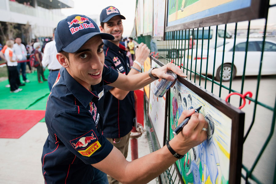 Sebastien Buemi and Jaime Alguersuari sign childrens paintings