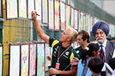 Heikki Kovalainen signs a painting at the Buddh circuit