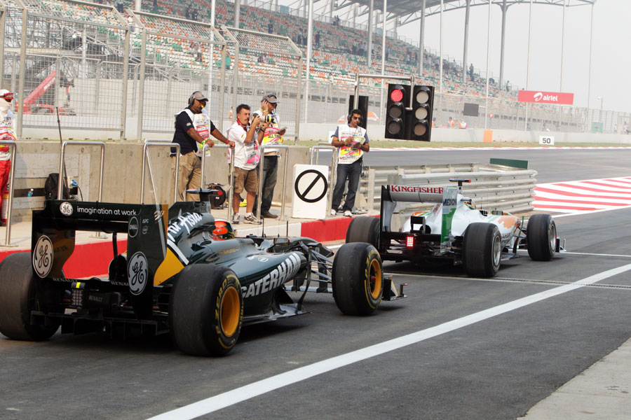Adrian Sutil beats Karun Chandhok to the end of the pit lane