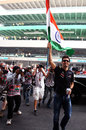 Mark Webber salutes the fans in the grandstand with an Indian flag