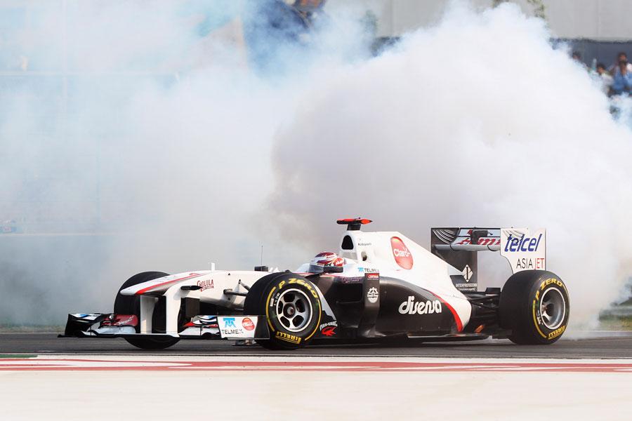 Smoke pours from the back of Kamui Kobayashi's Sauber