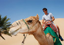 Mark Webber rides a camel on a Sand Dune Safari