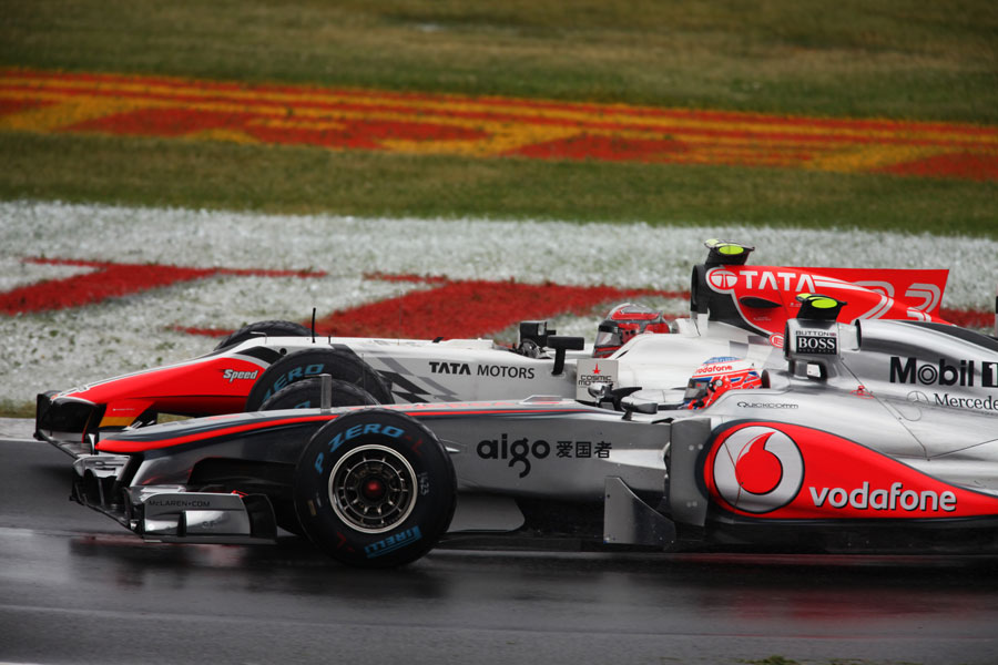 Jenson Button goes round the outside of Tonio Liuzzi