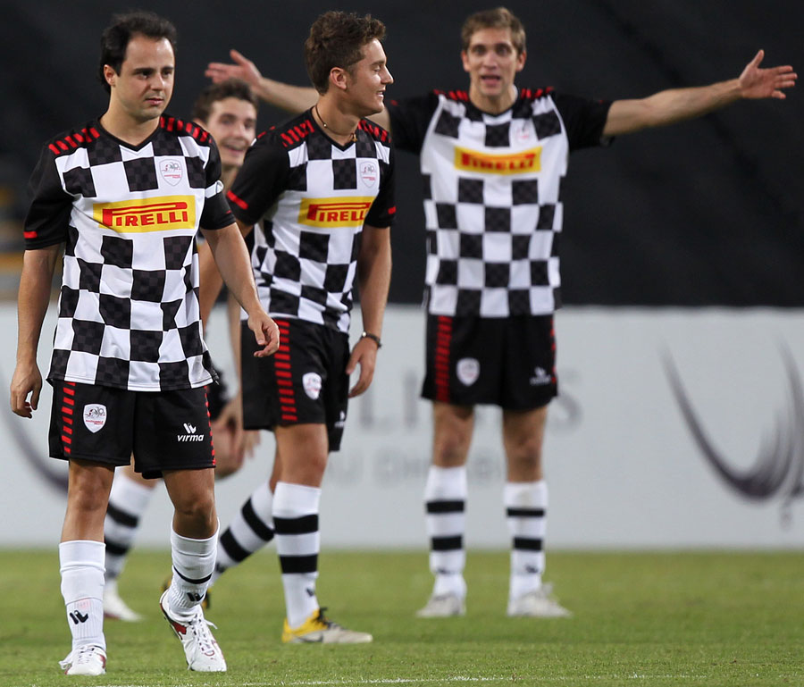 Vitaly Petrov shouts instructions to Stefano Coletti and Felipe Massa during a charity match