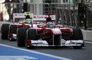 Felipe Massa follows Fernando Alonso down the pit lane