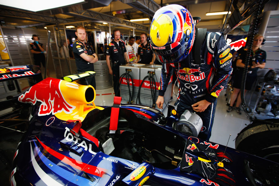 Mark Webber climbs in to his Red Bull ahead of FP1
