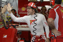 Fernando Alonso greets his mechanics in the Ferrari garage
