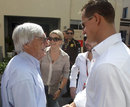 Bernie Ecclestone greets Michael Schumacher in the paddock on Sunday morning