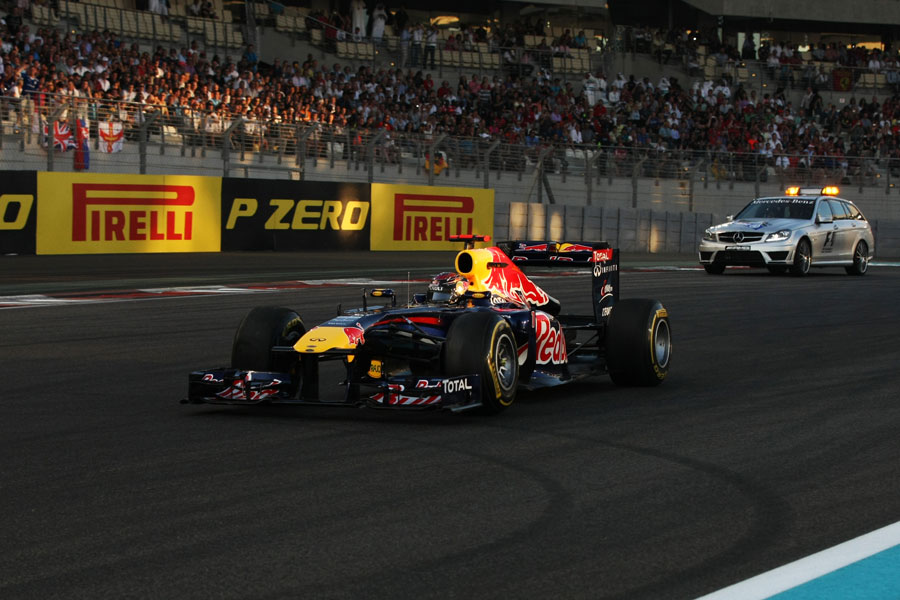 Sebastian Vettel is followed back to the pits with a deflated right rear tyre by the medical car