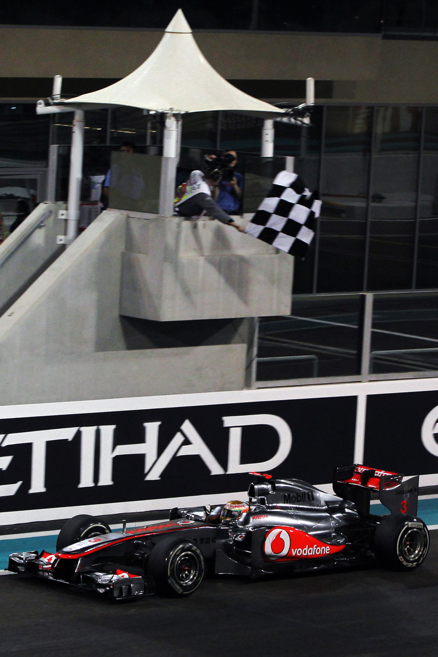 Lewis Hamilton celebrates as he takes the chequered flag
