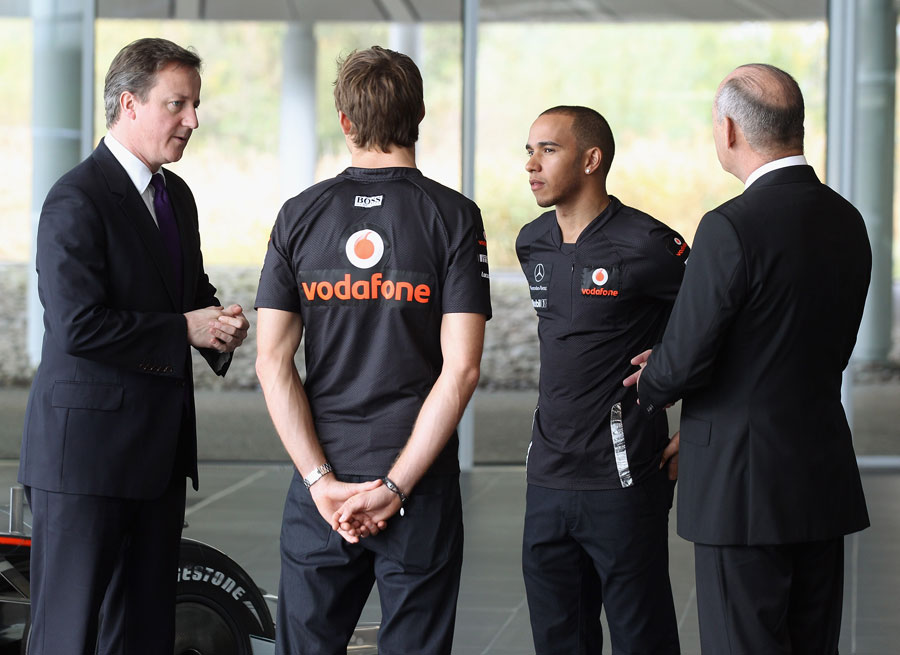 British Prime Minister David Cameron talks to Jenson Button, Lewis Hamilton and Ron Dennis during a visit to the McLaren Technology Centre