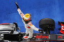 Lewis Hamilton celebrates on top of his McLaren