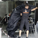 A McLaren mechanic covers up a chassis in the garage