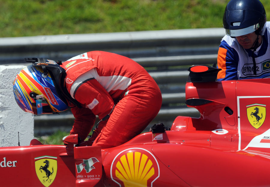 Fernando Alonso climbs out of his Ferrari after stopping with an engine problem