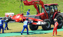 Fernando Alonso watches his Ferrari being lifted away