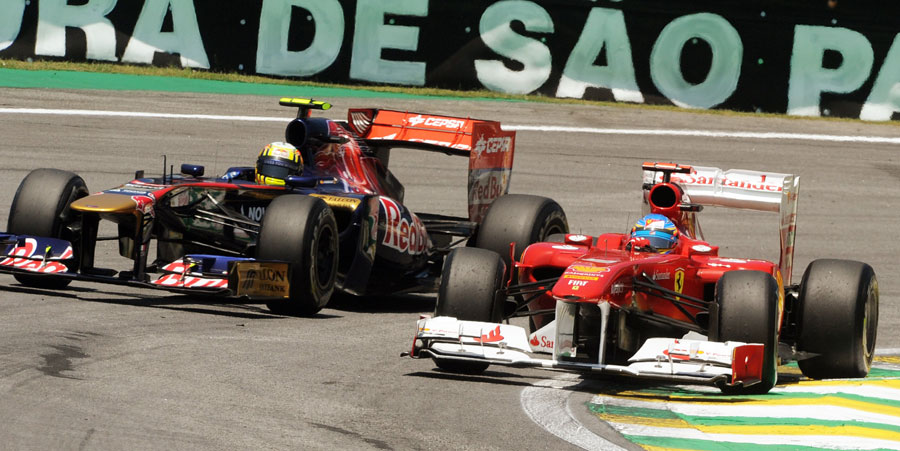 Fernando Alonso squeezes past Jaime Alguersuari in the first corner