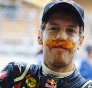 Sebastian Vettel celebrates beating Nigel Mansell's record for the most pole positions in one season by wearing a fake moustache