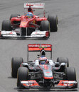 Jenson Button holds off Fernando Alonso early in the race