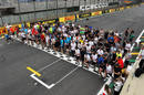 Members of the Formula One paddock run the track for charity