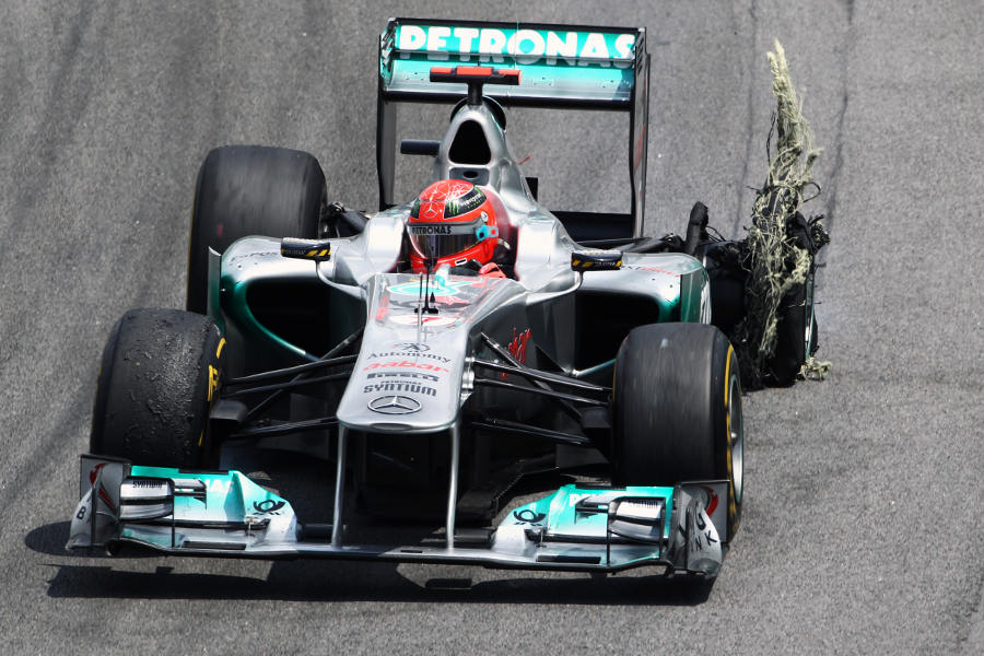 Michael Schumacher limps back to the pits with a puncture