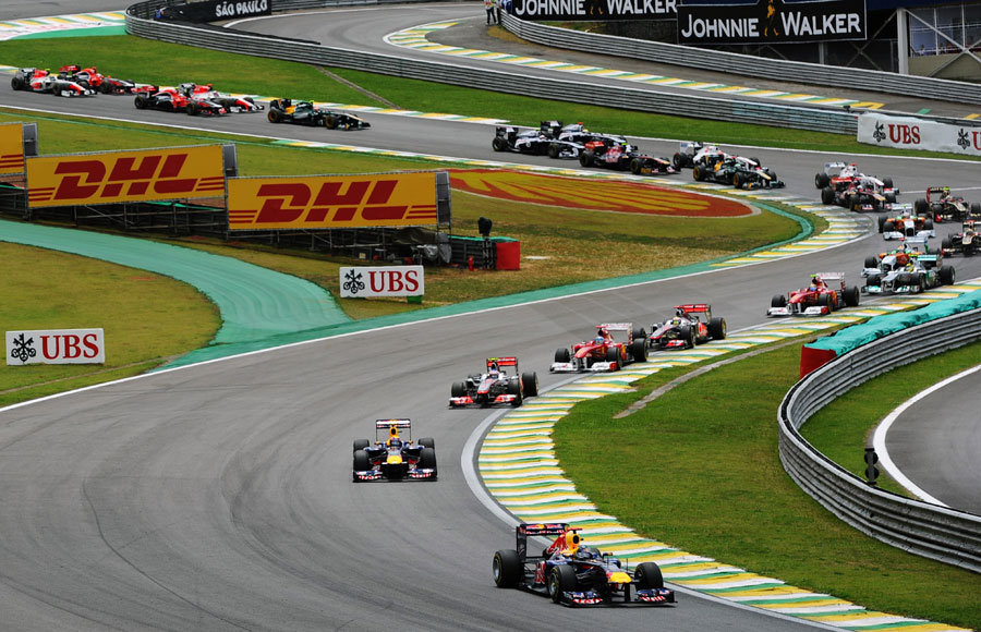 Sebastian Vettel leads the field through the Senna Esses at the start of the race