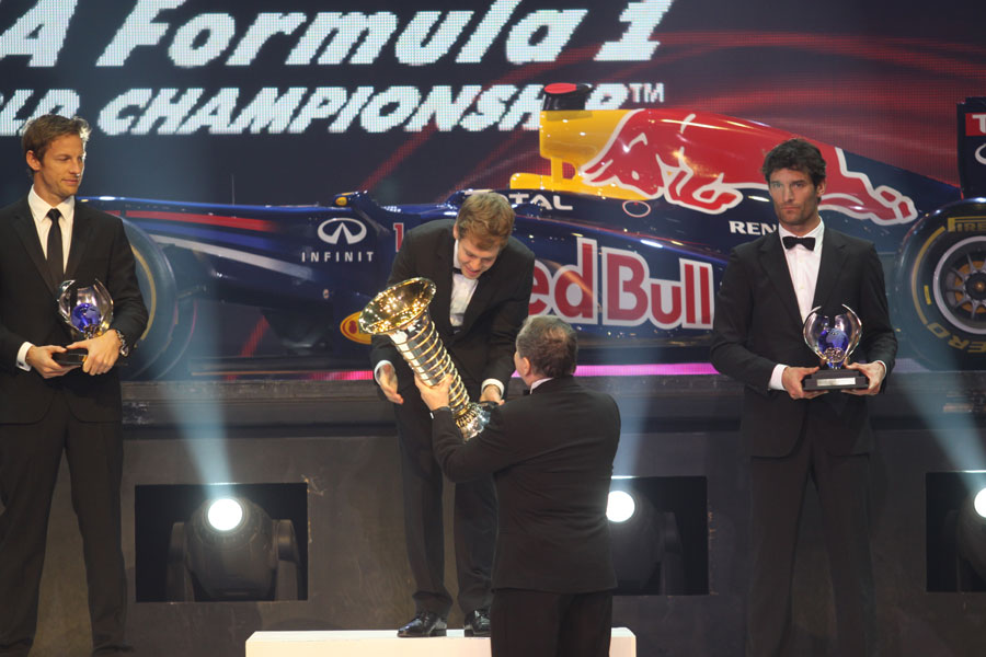 Sebastian Vettel receives his drivers' championship trophy from Jean Todt