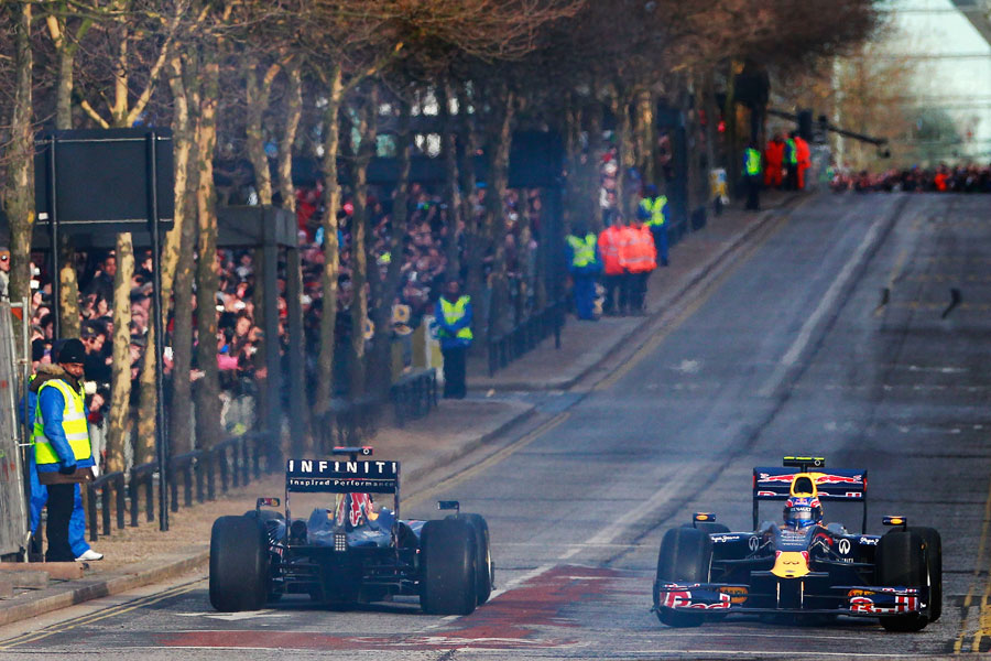 Mark Webber and Sebastian Vettel cross paths on a demonstration run