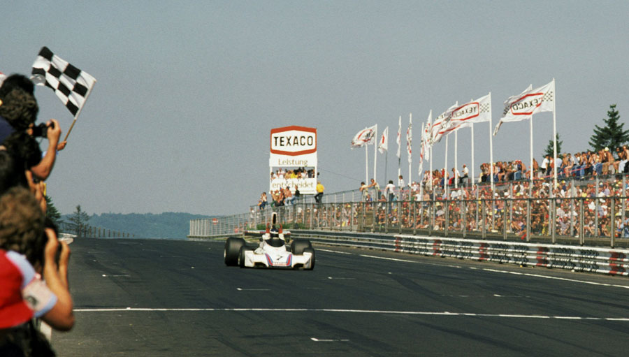Carlos Reutemann celebrates as he takes the chequered flag