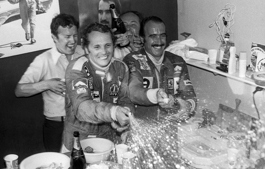 Niki Lauda celebrates his first title alongside team-mate and race winner Clay Regazzoni