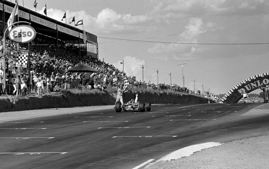 Jim Clark crosses takes the chequered flag in the Lotus 49
