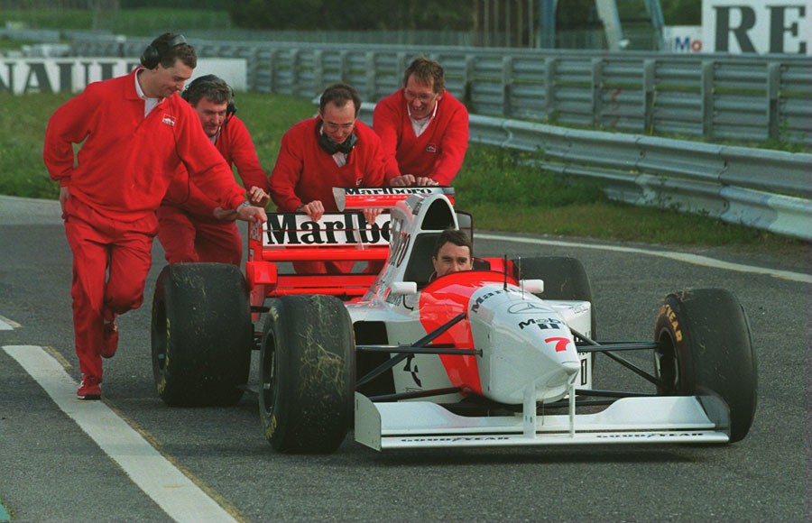 McLaren mechanics push Nigel Mansell back down the pit lane after he spun off during his first test for the team